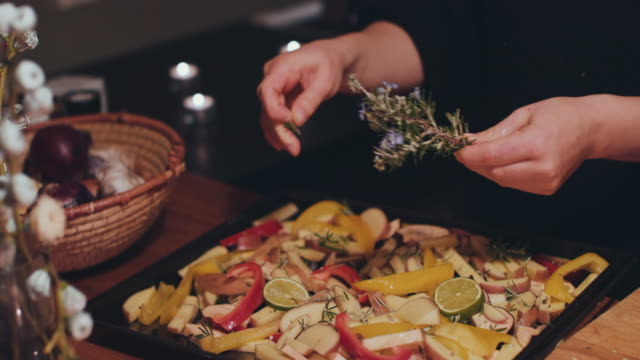 woman putting fresh rosemary on roasted vegetables - sprinkles stock videos and b-roll footage