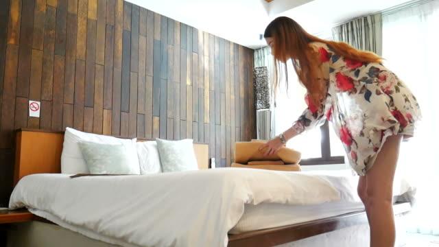 frau setzen frische handtücher auf dem bett - luxus hotel stock-videos und b-roll-filmmaterial