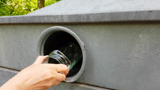 Woman Putting Glass Jars Into Bottle Bank