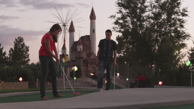 WS Woman putting golf ball and high fiving with man / Orem, Utah, USA