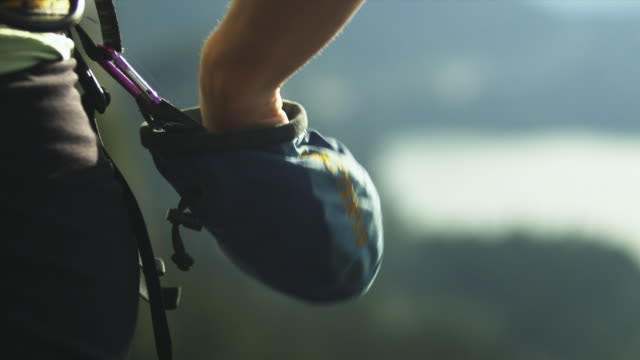vídeos de stock, filmes e b-roll de cu r/f ha woman putting hand into rosin bag gripping onto cliff with landscape in background, squamish, british columbia, canada - pacote de talco