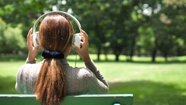 SLO MO Woman Putting headphones in ears for Listening to music in Park, Relaxing