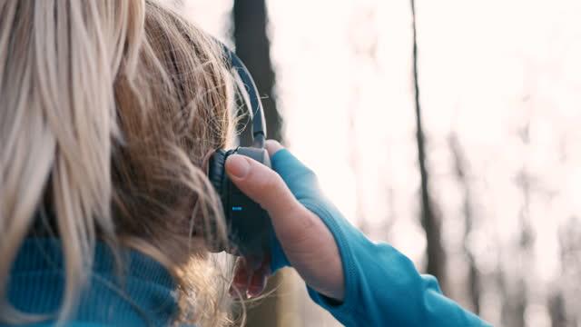vídeos y material grabado en eventos de stock de slo mo mujer poniéndose los auriculares antes de empezar a correr en el bosque - auriculares una persona escapismo vista posterior cabeza y hombros