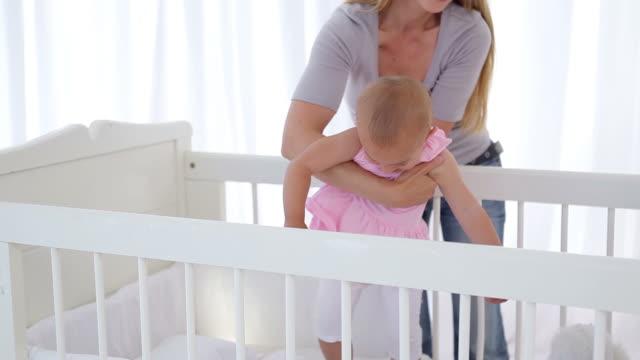 vidéos et rushes de woman putting her baby girl in a cradle - vêtement de bébé