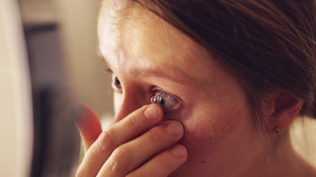 woman putting in contact lens. - inserting stock videos & royalty-free footage