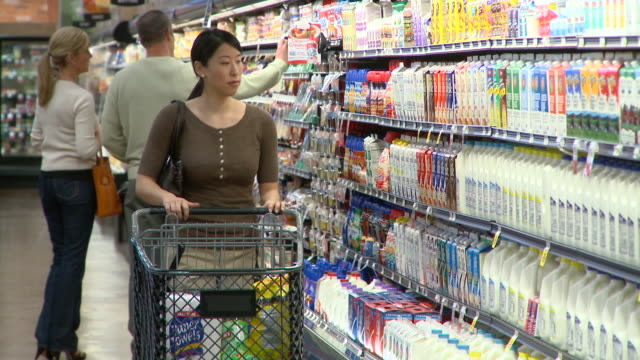 ms selective focus woman putting milk in shopping trolley  shopping in supermarket, richmond,  virginia, usa - milchprodukte stock-videos und b-roll-filmmaterial