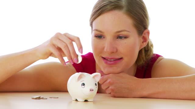 woman putting money in piggy bank - 25セント硬貨点の映像素材/bロール