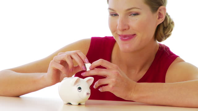 stockvideo's en b-roll-footage met woman putting money in piggy bank - amerikaanse munt