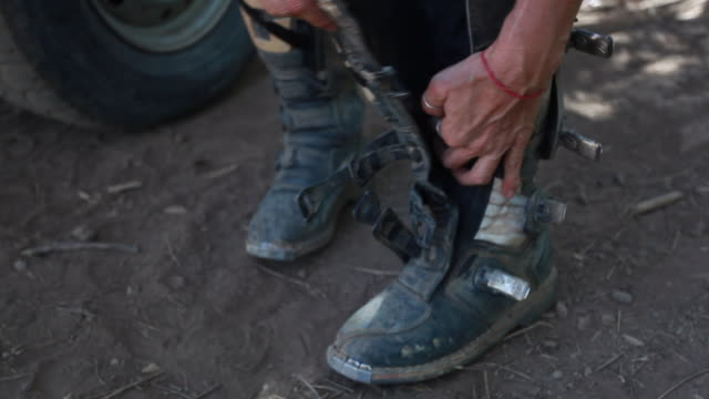 vidéos et rushes de a woman putting on and strapping dirt bike boots to her feet on a hot summer day - kelly mason videos