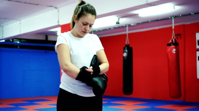 vídeos y material grabado en eventos de stock de mujer poner guantes de boxeo - guante de boxeo