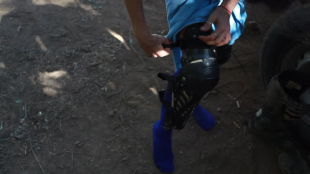a woman putting on dirt bike knee pads on a hot summer day - kelly mason videos stock-videos und b-roll-filmmaterial