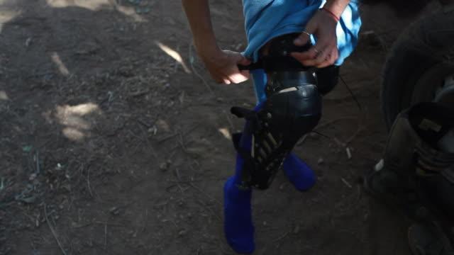 vidéos et rushes de a woman putting on dirt bike knee pads on a hot summer day - kelly mason videos