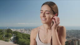 Woman putting on earphones in city of Barcelona. Girl listening music in earbuds