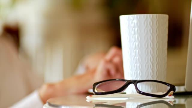 vídeos y material grabado en eventos de stock de mujer poniendo anteojos mientras trabajaba en casa - esmalte de uñas rojo