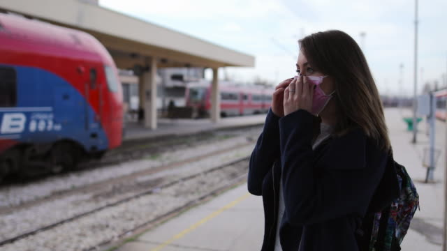 vídeos de stock e filmes b-roll de woman putting on face mask for protection of virus at train station - esperar