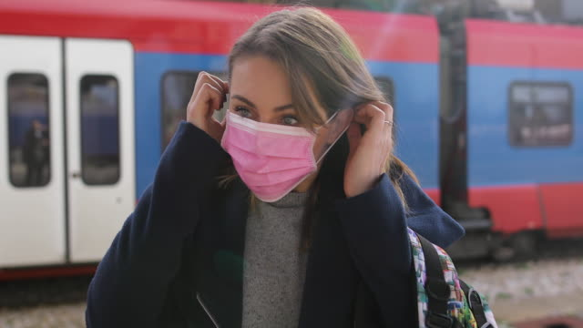woman putting on face mask for protection of virus at train station - train vehicle stock videos & royalty-free footage