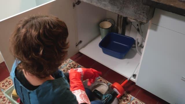 vídeos de stock, filmes e b-roll de woman putting on gloves before unclogging the drain - chão de cerâmica