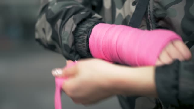 woman putting on hand wrap before her exercise - camouflage clothing stock videos & royalty-free footage