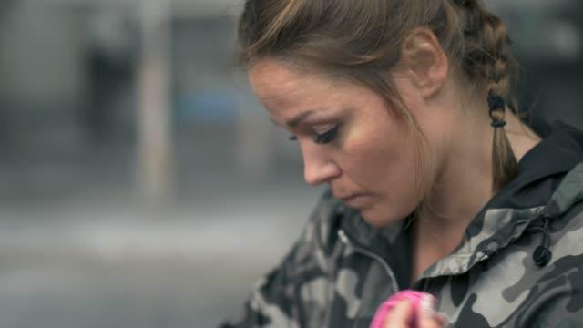 vídeos y material grabado en eventos de stock de mujer poniendo en mano envuélvalas antes de su ejercicio - ropa de camuflaje