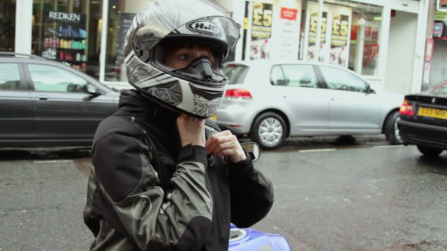 MS Woman putting on helmet and gloves, standing by motorcycle on street / London, United Kingdom