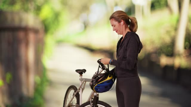 vidéos et rushes de woman putting on helmet, going for bike ride on sunny day in the park - motard