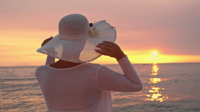 slo mo donna tenendo il suo cappello sulla spiaggia - camicetta video stock e b–roll