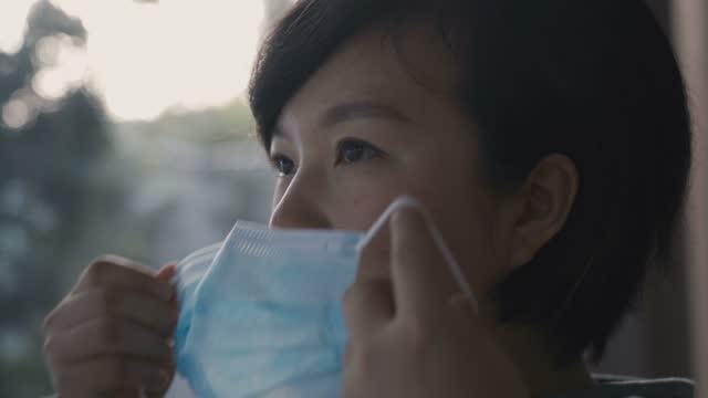 vídeos y material grabado en eventos de stock de mujer poniéndose su máscara protectora antes del trabajo - epidemiología