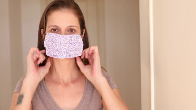 woman putting on homemade protective mask - home made stock videos & royalty-free footage