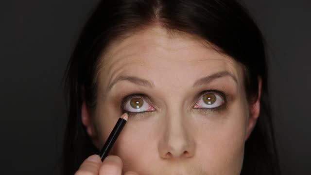 ECU Woman putting on kohl eyeliner / Copenhagen, Denmark