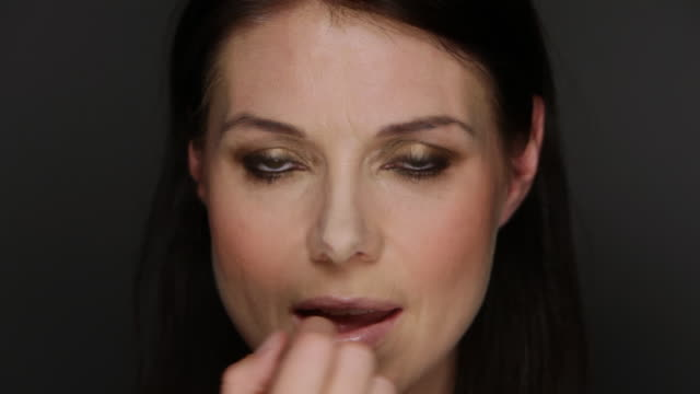 cu woman putting on light lipstick / copenhagen, denmark - applying stock videos and b-roll footage