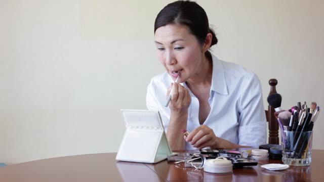 woman putting on lipstick - 口紅点の映像素材/bロール