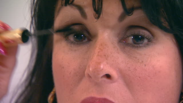 Woman putting on mascara, close up
