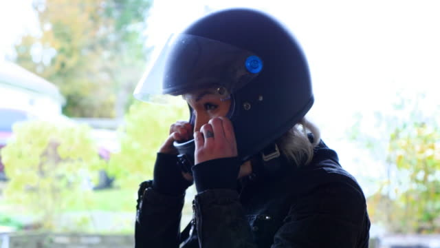 Woman putting on motorcycle helmet while getting ready for ride