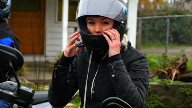 Woman putting on motorcycle helmet while getting ready for ride with friends