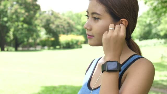 Woman putting on music and checking smart watch before exercising