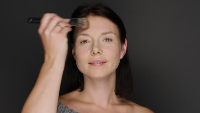 ms woman putting on powder with brush / copenhagen, denmark - blusher make up stock videos and b-roll footage