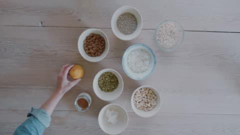 woman putting orange next to bowls - ハイチ点の映像素材/bロール