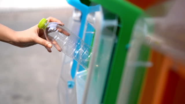 slo mo woman putting plastic bottles in recycle bin garbage - lanciare video stock e b–roll