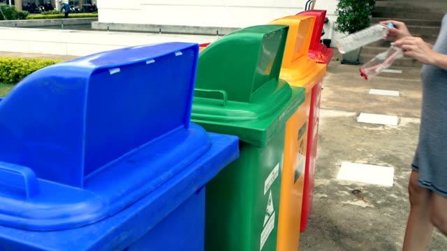 vídeos y material grabado en eventos de stock de mujer poniendo en contenedor de reciclaje de botellas de plástico. - contenedor para la basura