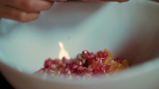 woman putting pomegranate in fruit salad in bowl - fruit salad stock videos & royalty-free footage