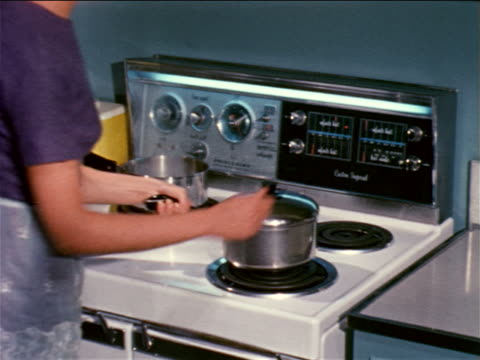 1961 woman putting pot on stove + turning knob / industrial - stay at home mother stock videos & royalty-free footage