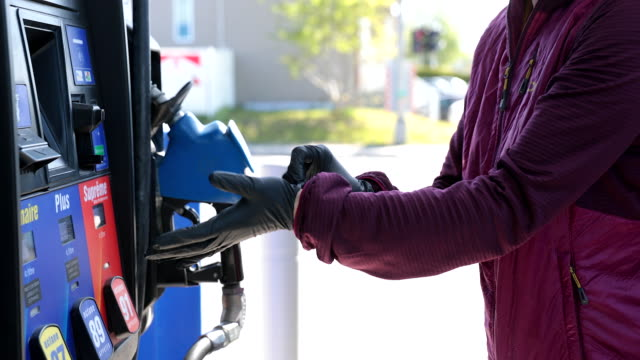 woman putting protective gloves at gas station during covid-19 - fuel pump stock videos & royalty-free footage