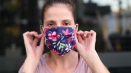 Woman putting protective mask on close up