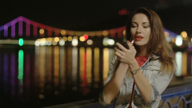 woman putting red lipstick outside at night city lights reflecting in the water in kiev - hoop earring stock videos and b-roll footage
