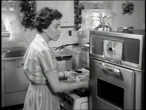 B/W 1959 woman putting roast on glass tray into early microwave oven in kitchen
