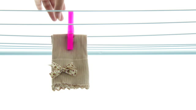 stockvideo's en b-roll-footage met woman putting socks on a clothesline - wasknijper