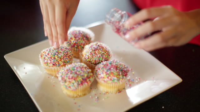 CU woman putting sprinkles on cupcakes.