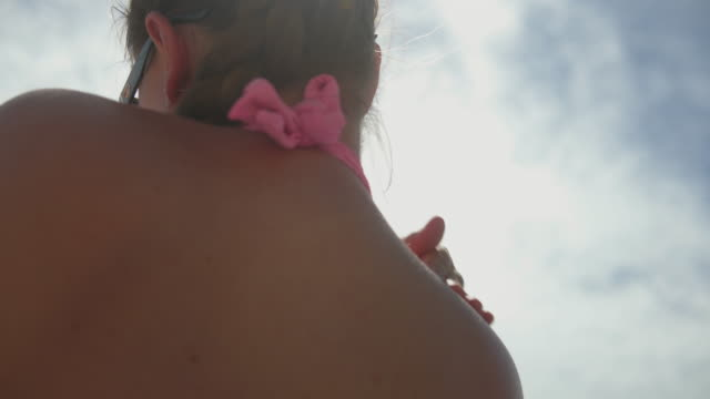 woman putting suntan lotion on at the beach. - uv protection stock videos and b-roll footage