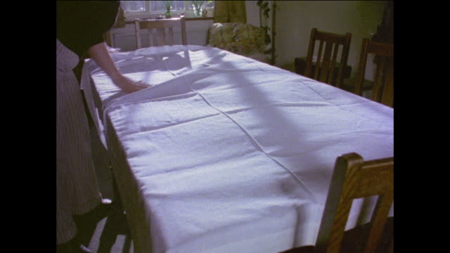 stockvideo's en b-roll-footage met montage woman putting tablecloth on dining table / man preparing food for a party / united kingdom - 1977