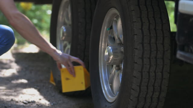 woman putting tire blocks or wheel chocks on camper trailer. - camper trailer stock videos and b-roll footage